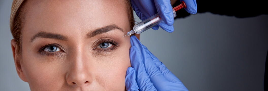 Woman receiving cosmetic procedure with syringe