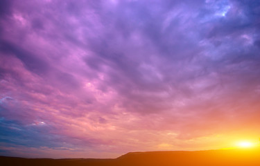 Photo of a violet sunset with clouds and sun