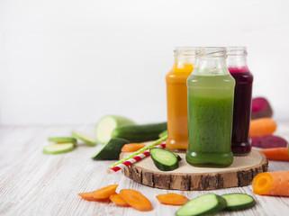 Freshly squeezed vegetable juice in bottles, useful vitamin cocktail, detox diet, selective focus