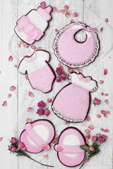 Cookies with glaze in the form of dress,baby body,shoes,bottle milk with petals of dried roses. On white wooden surface.