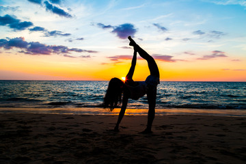 Silhouette sport woman stand yoga on the sea beach