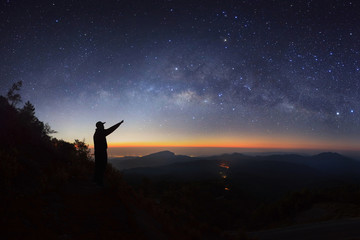 A Man is standing next to the milky way galaxy pointing on a bright star at Doi inthanon Chiang mai, Thailand.