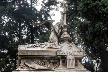 Sculpture of an angel kissing the cross on the sarcophagus on a cemetery