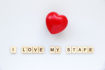 I LOVE MY STAFE text word made with wood blocks and Red Heart on table White.