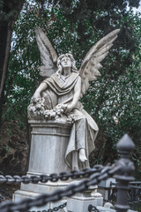 Sculpture of a sad angel on a cemetery against the background of leaves