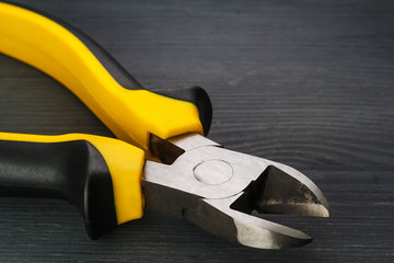 Electrician tools. Side cutters on a dark wooden table.