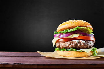 Craft beef burger on wooden table isolated on black background.