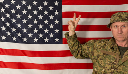 Soldier showing victory sign on the background of the USA flag.