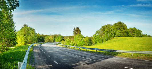 Wall Mural - asphalt road panorama in countryside on sunny spring evening
