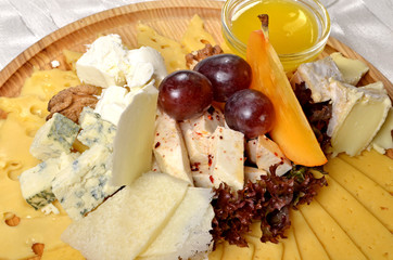 Cheese and some fruits on the wood plate