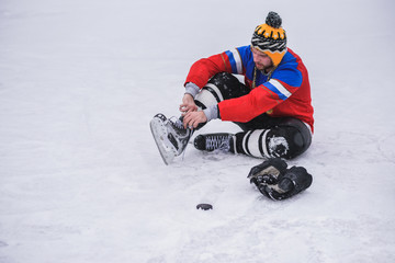 hockey player sitting on the ice to tie shoelaces