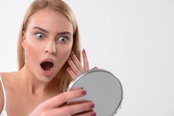 Shocked girl observing pimple on her face