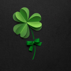 Good luck / Creative St. Patricks Day concept photo of a shamrock made of paper on black background.