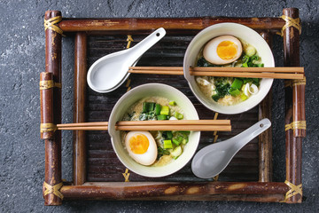 Two bowls with asian style soup with scrambled eggs, half of marinated egg, spring onion, spinach served with wood chopsticks and spoons on bamboo tray on black concrete background. Top view