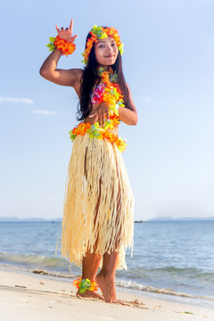 Hula Hawaii dancer dancing on the beach with horizon of sea. Ethnic woman in costume dancer Hawaii hula dancing in a tropical island.