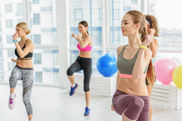 Smiling sportive young women in gym