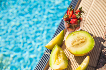 melon and strawberries near the swimming pool in summer