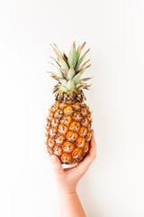 Female hand holding ripe pineapple on a white background