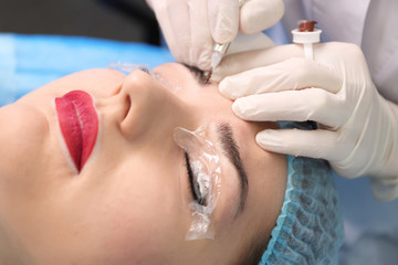 Young beautiful woman making permanent makeup in cosmetology salon