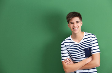 Happy teenage boy in casual clothes on color background Wall mural