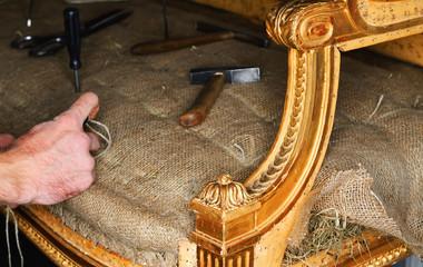 Ein Polsterer repariert ein altes Empire Sofa