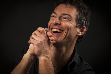 Close up portrait of hard laughing  man. Isolated on black background