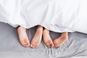 Child feet on bed. Adorable little girl awaking up in her bed. morning. Child feet under the white blanket.