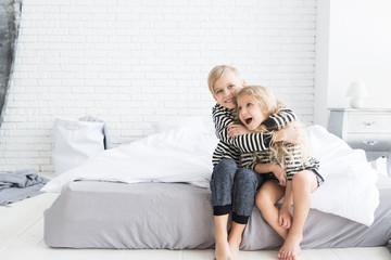 girl with white curly hair in a striped vest and a  boy with blond hair in a striped vest  in bedroom. Children having fun. Brother and sister. Blonde children
