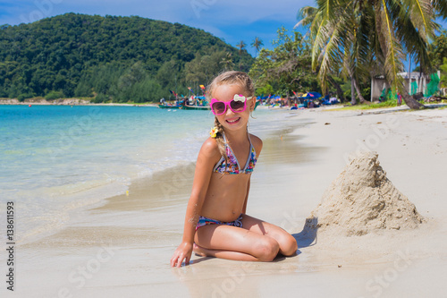 13179b9a7e83b cute little girl in sunglasses and a swimsuit on the beach in paradise by  the sea. Travel and Vacation. Freedom Concept