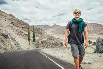 Traveler walks on the mountain road in indian Himalaya