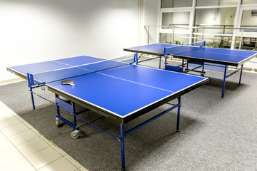 Two blue ping pong tables in the room