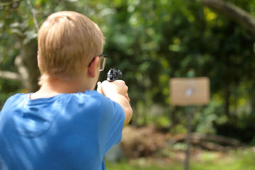 Young boy practice shooting guns on outdoor