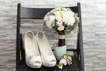 Bride`s wedding accessories: wedding shoes, rings and bouquet or boutonniere with white flowers