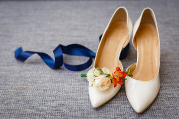 Bride`s wedding accessories: wedding shoes, rings and bouquet or boutonniere with red and white flowers
