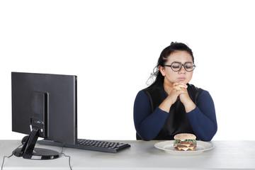 Obese female hesitates eat donuts on studio