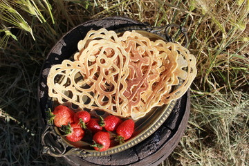 Pancakes in heart shape with icing sugar and strawberries on the side, with wheat in the background on sunny summer afternoon