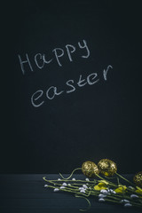 Decorative willow twigs with Easter eggs on a wooden background. The inscription in chalk: Happy Easter.