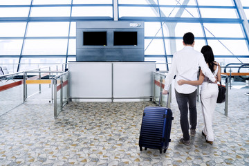 Young couple with suitcase at airport terminal