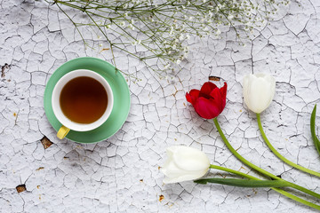 Cup of tea with Floral background with red and white tulips and daisies
