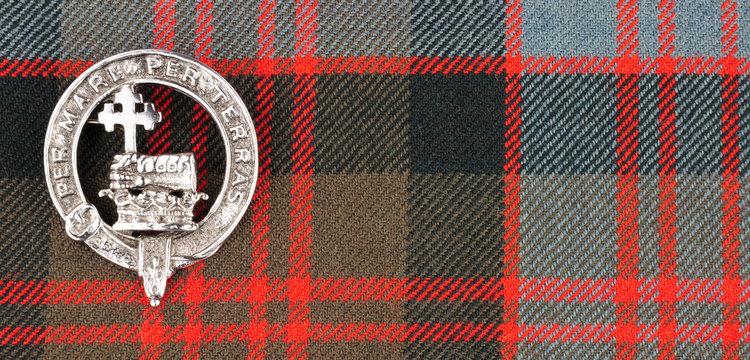 Scottish MacDonald Clan Family Crest On Tartan Fabric Background