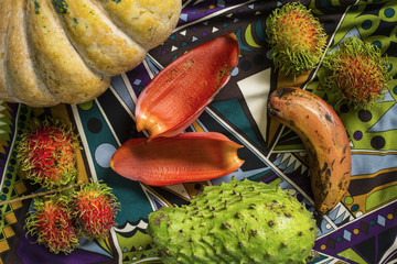 Table with pumpkin, rambutans, soursup and red banana. Still life composition with tropical fruits and vegetables.