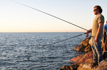 Young fisherman at sunset