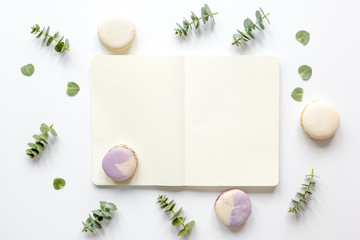 woman table with notebook, macaroons and eucalyptus top view mock-up