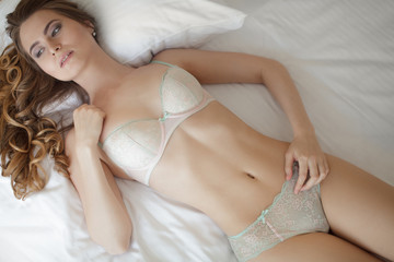 portrait of young woman in underwear lying in bed