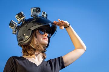Une jeune femme regardant l'horizon, porte un casque avec quatre caméras de sport fixées dessus
