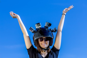 Une jeune femme , les bras levés, porte un casque avec quatre caméras de sport fixées dessus