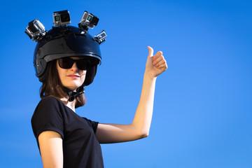 Une jeune femme, le pouce levé, porte un casque avec quatre caméras de sport fixées dessus
