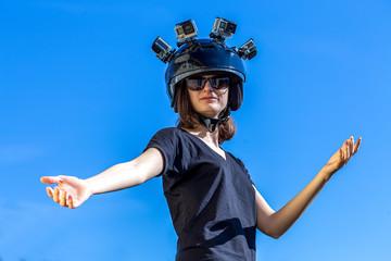Une jeune femme, porte un casque avec quatre caméras de sport fixées dessus