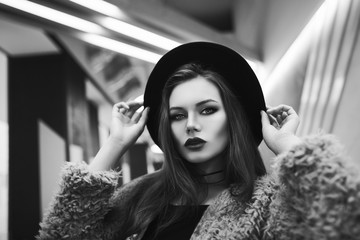 Monochrome indoor close up portrait of young attractive fashionable confident woman looking at camera. Model wearing stylish fake fur coat, wide-brimmed hat. Beautiful geometric lights on background