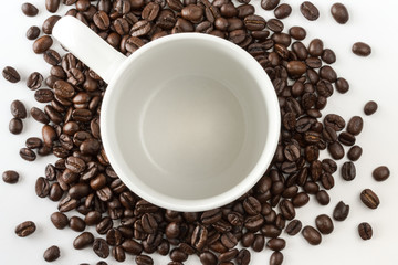 Empty coffee cup surrounded by whole coffee beans